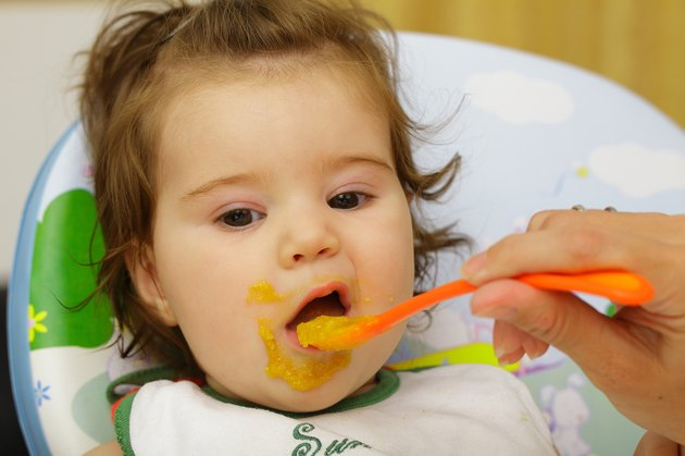 Baby being fed with food around mouth