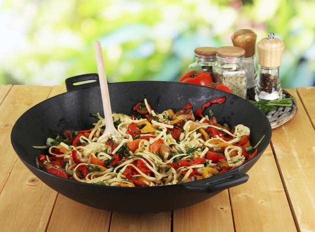 Noodles with vegetables in wok on nature background