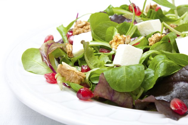 Mix salad with pomegranate, cheese and nuts