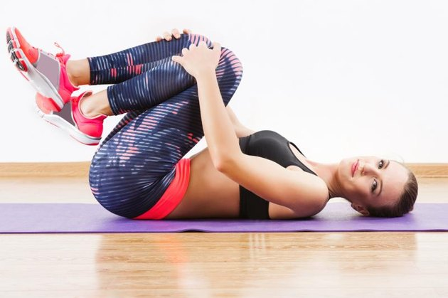 Pretty girl with dark hair wearing pink snickers, dark leggings and black short top doing exercises on mat at gym, fitness, wooden floor, copy space.