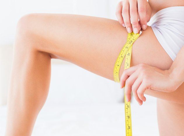 Slim woman measuring her thigh