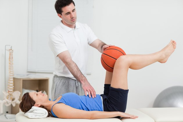Physiotherapist placing a ball between the knees of woman