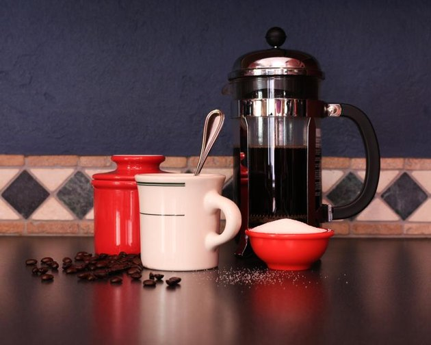 Still life of a French press with white coffee cup, sugar, coffee beans with red accents on a blue textured wall with diamond design tile.