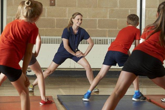 Teacher Taking Exercise Class In School Gym
