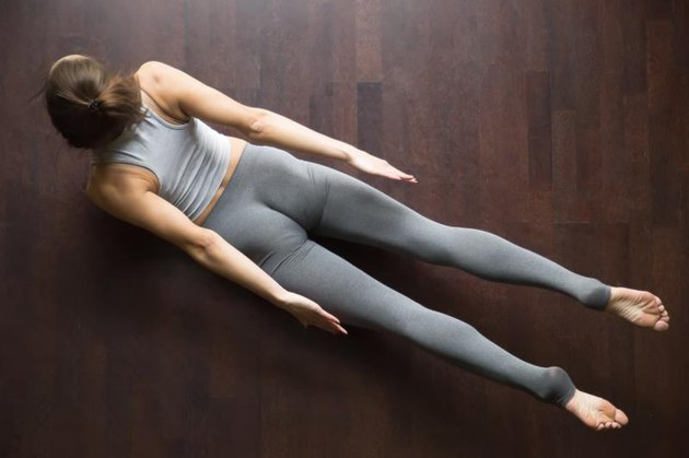 Beautiful young model working out in home interior, doing yoga or pilates exercise on wooden floor. Double Leg Kicks, Salabhasana, Locust pose. Top view. Full length