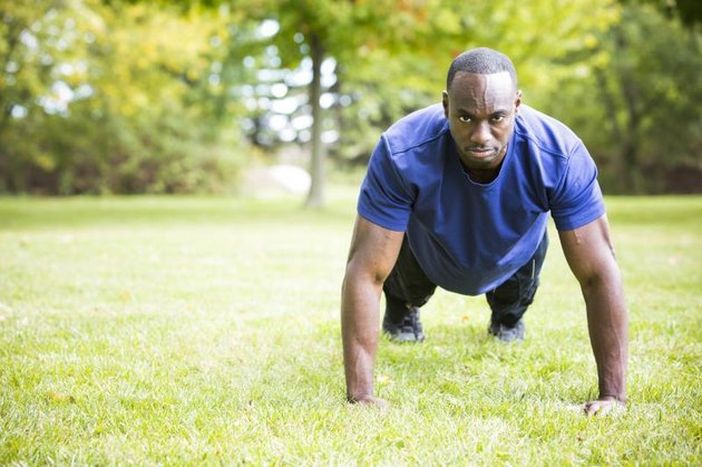 young black man wearing athletic wear doing exercise in the fall park