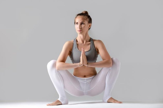 Young attractive woman practicing yoga, sitting in Garland exercise, Malasana pose, working out wearing sportswear, white pants, gray top, indoor full length, isolated against grey studio background