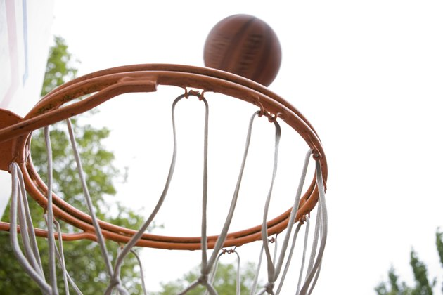 Basketball falling toward hoop on tree-shaded court
