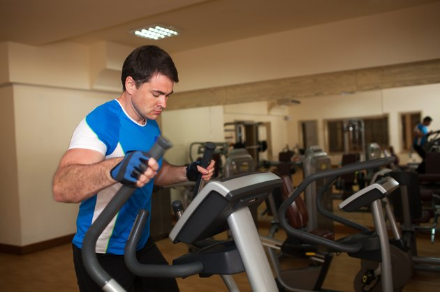 Man exercising on elliptical machine in gym