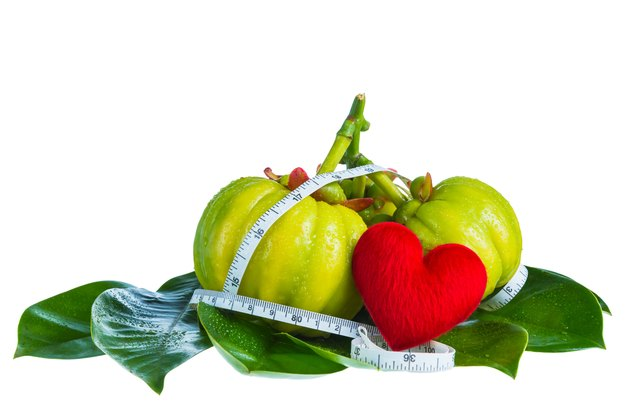 Garcinia cambogia with measuring tape, isolated on white backgro