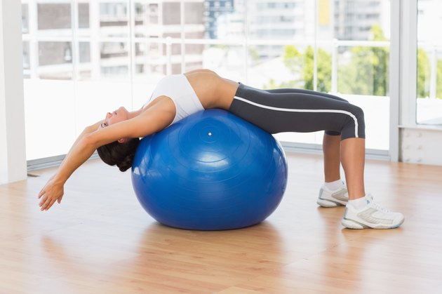 Fit woman stretching on exercise ball at gym