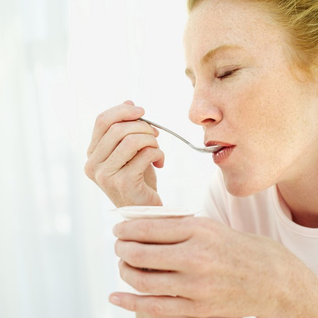 Close-up of a young woman eating strawberry yoghurt with a spoon