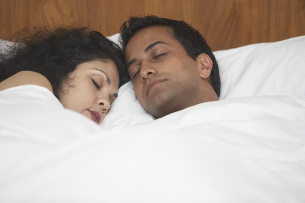 Middle Eastern couple sleeping in bed