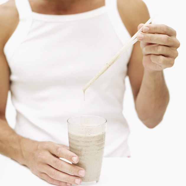 Young man holding a straw over a glass of milkshake