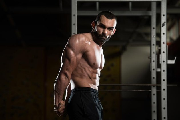 Youn, muscular man with a beard standing in a dark gym, flexing his biceps, shoulders, triceps, pecs and abs.