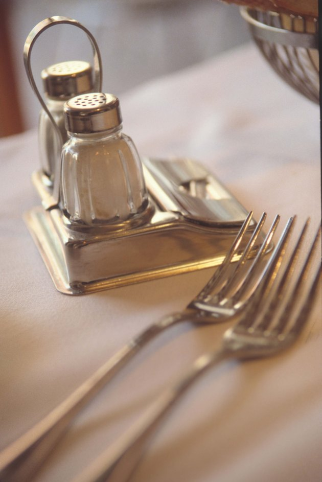 Salt and pepper shakers on table with forks