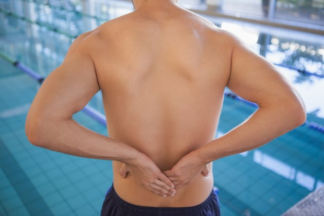 Fit swimmer touching his back by the pool