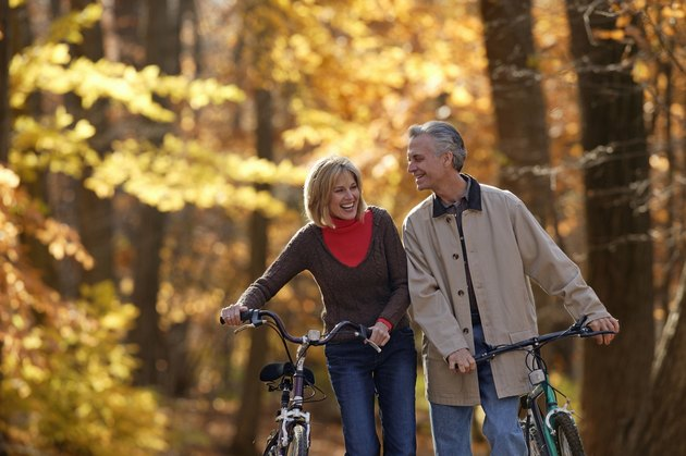 Couple walking bicycles through fall forest