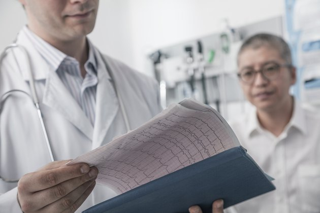 Doctor checking medical chart with patient in the background