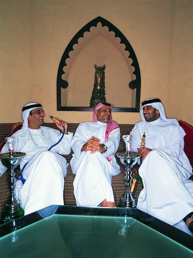 Three Men in Traditional Middle Eastern Dress Smoking Hookahs Sitting on a Sofa