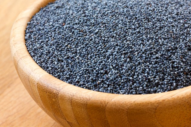 Detail of poppy seeds in wood bowl on wood surface.