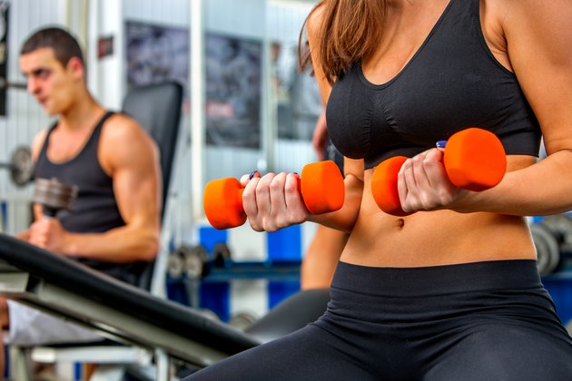 Group of people  working with dumbbells  at gym