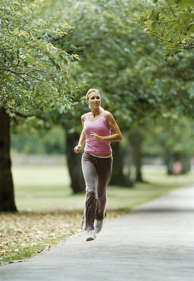 Woman in a Pink Vest Jogging on a Path through a Park
