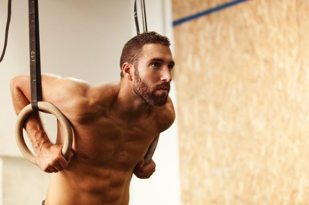 Young fit man is preparing for pulling up on gymnastic rings.
