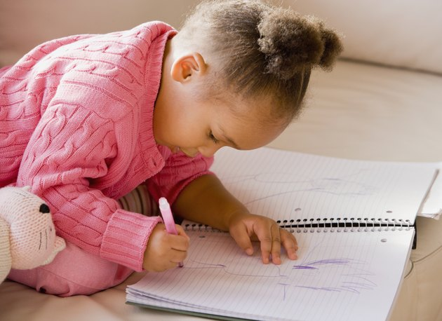 African girl drawing in notebook