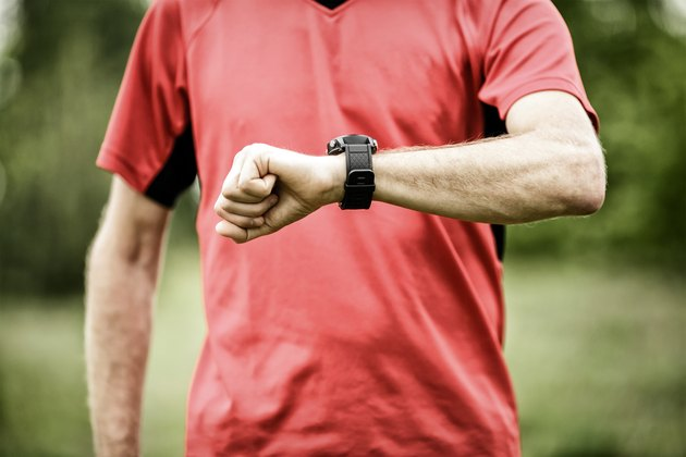Runner looking at sport or smart watch checking pulse
