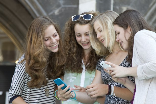 Teenage friends text messaging on cell phones