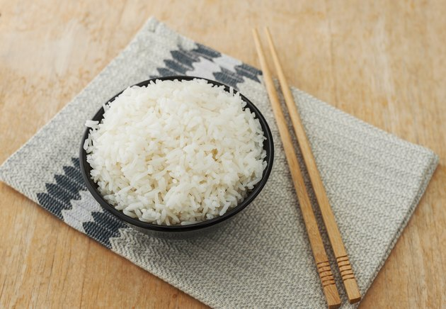 White rice in black bowl with wood chopsticks
