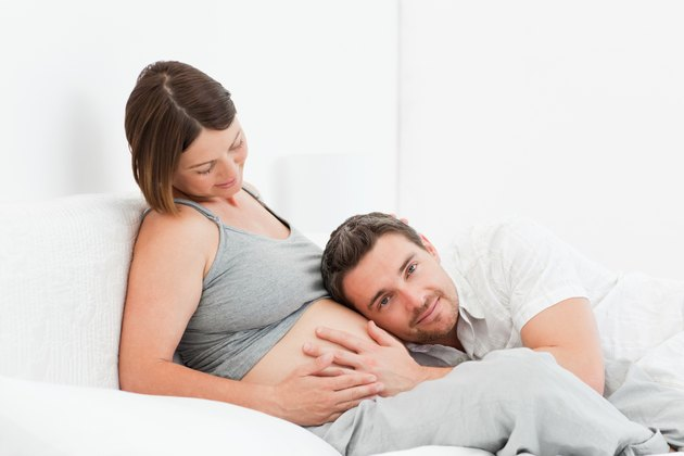 Husband listening to his wife's belly