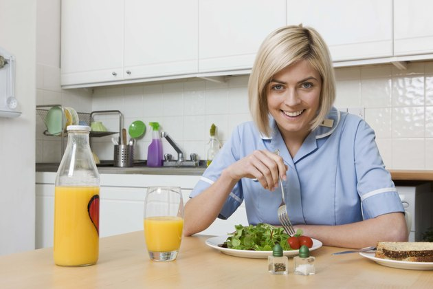 Woman eating salad with orange juice