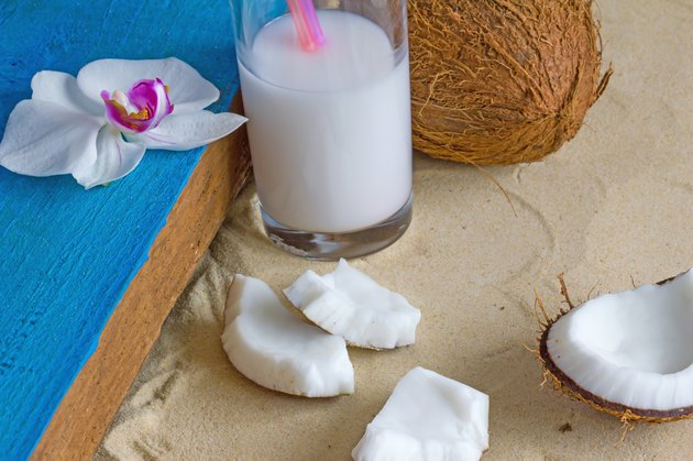 Relaxation at the beach with coconuts, coconut milk and orchid