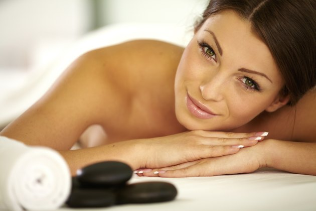 Young female getting stone massage in spa