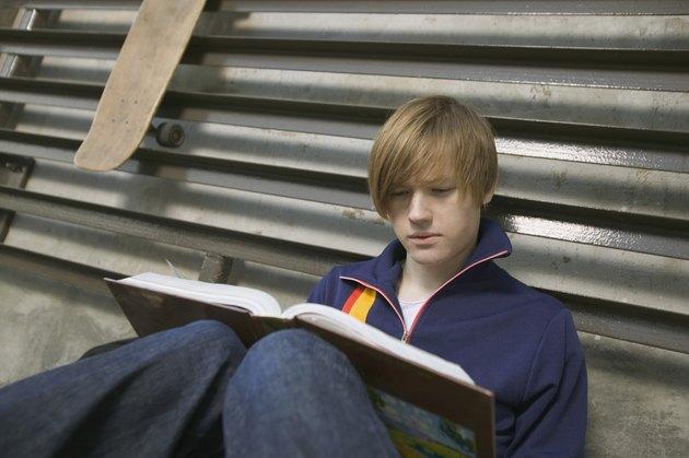 Teenage boy reading book outdoors