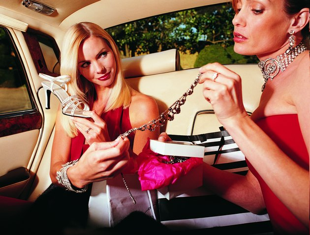 Young Glamorous Women Sitting in the Back of Car Holding Jewellery