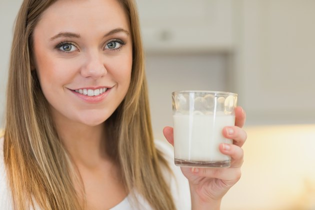Happy woman holding glass of milk