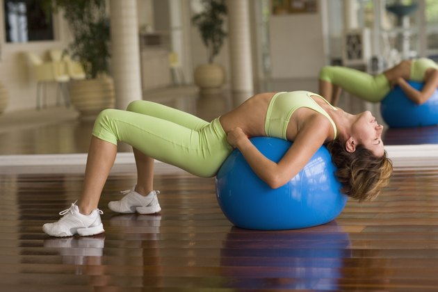 Woman stretching on exercise ball next to mirror