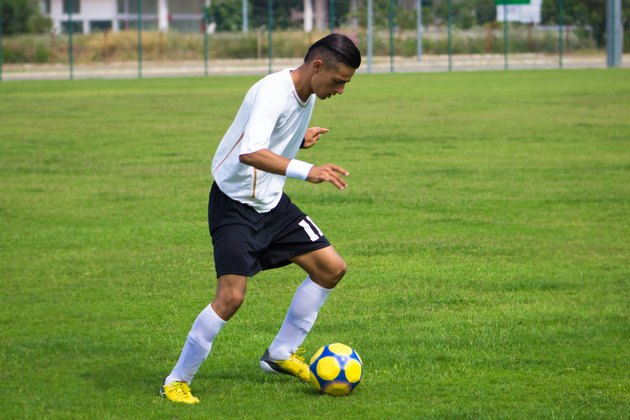 Young man playing soccer on soccer field