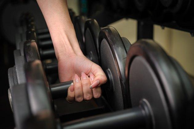 Female hand holding dumbbell