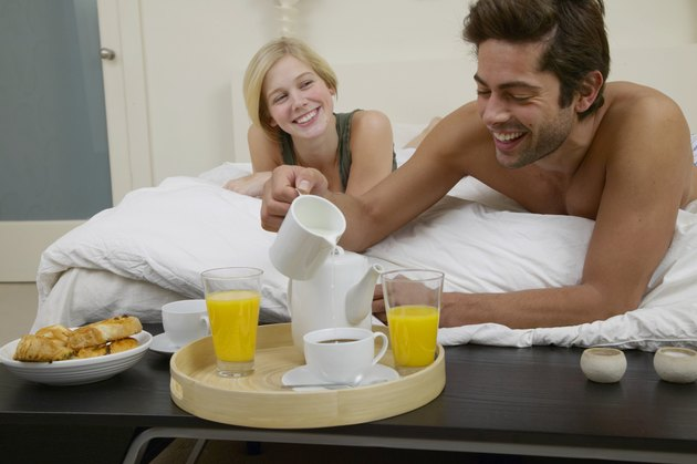 Couple in bed, man leaning to make drink on breakfast tray, smiling