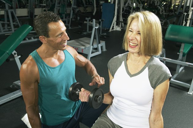 Male fitness instructor training senior woman in gym, smiling