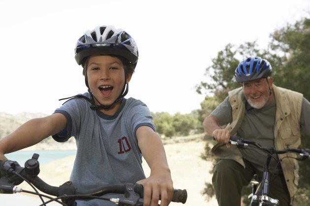 Grandson (5-7) and grandfather riding bikes, portrait (focus on boy)