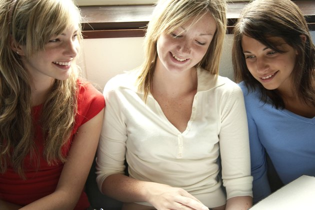 """""""Three female teenage students (14-16) looking at book, smiling"""""""