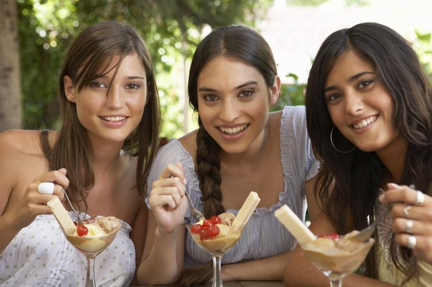 Teenage girl (16-18) and two young women eating dessert, portrait