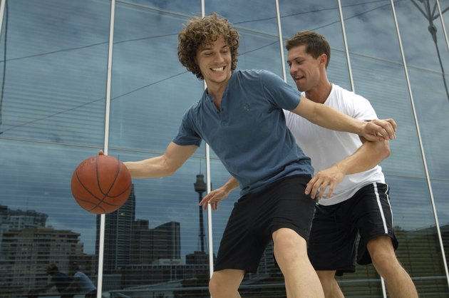 Two young men playing basketball outside office