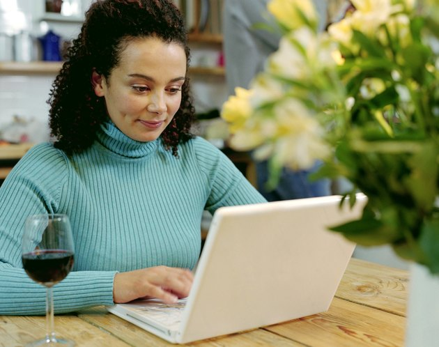 Woman using laptop at table indoors