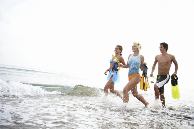 Three friends running in water on beach, holding flippers, smiling